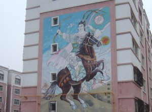 Mural of a man brandishing a bow on horseback viewed on the end of a tenement block in Barkul/Balikun in Xinjiang province, China.