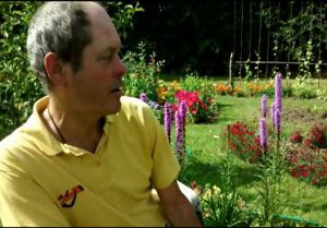 Profile of middle-aged caucasian male in a sunny garden with flowers blooming